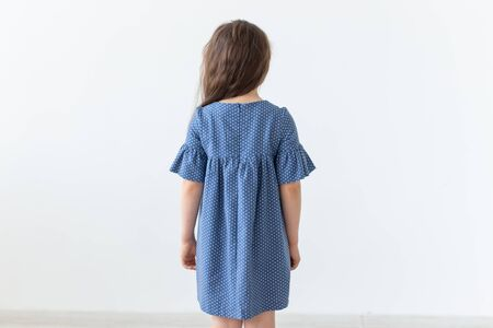 Rear view of little girl posing in blue polka dot dress on a white background. The concept of classic childrens clothing and stylish children.