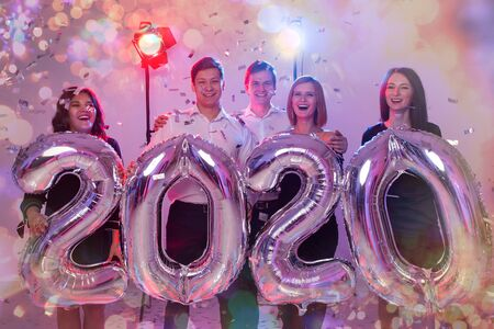 Party, people and new year holidays concept - women and men celebrating new years eve 2020