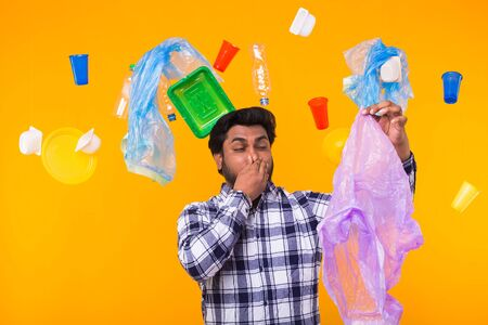 Environmental pollution, plastic recycling problem and ecology problem concept - surprised Indian man closing nose because he is felt bad smell from garbage on yellow background. 写真素材