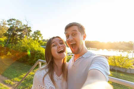 Capturing bright moments. Joyful young funny loving couple making selfie on camera while standing outdoors Stock Photo - 129849701