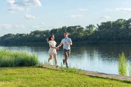 Love and relationship concept - The happy man and woman running in a park near a lake