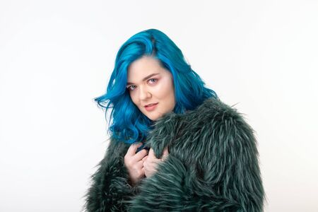 Animal protection, fashion and hair concept - beautiful girl with blue hair dressed in artificial fur coat standing on white background