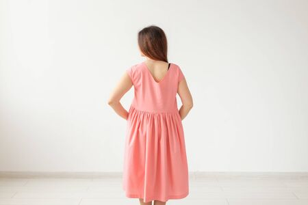 Beautiful young cheerful woman in a bright pink dress posing on the background of a white wall with copy space. The concept of stylish feminine images. Stock Photo