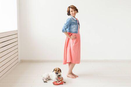 Young cheerful woman in a long dress and denim dress with her beloved dog posing on a white background. The concept of daily clothing.