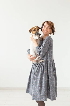 Charming smiling young woman in a stylish gray dress holding her favorite dog Jack Russell Terrier. Concept favorite dogs.