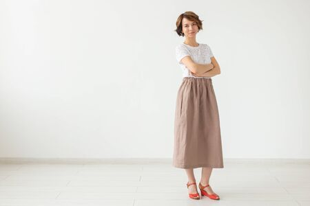 people, fashion and style concept - young woman posing in clothes in studio on white background.