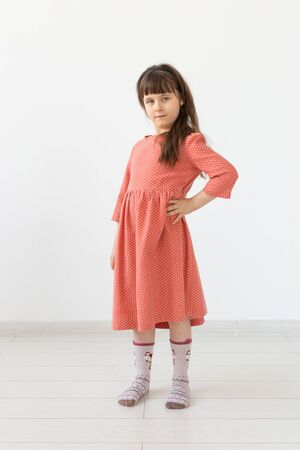 people, kids and fashion concept - little girl posing in clothes at studio.