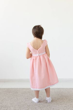 Fashion designer, kids and child concept - back view of little girl posing in clothes at studio
