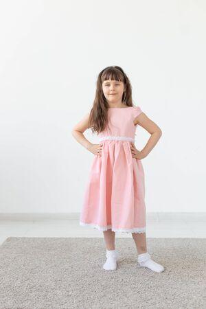 Little girl is a model, in a pink dress in studio
