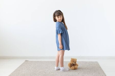 Child girl in blue dress with toy in white room