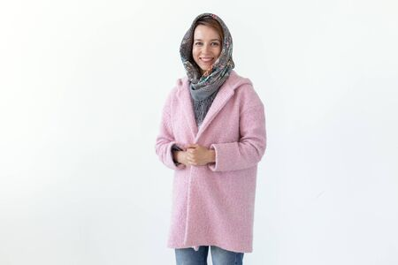 Positive young pretty woman posing in a scarf and a pink coat on a white background. Concept of autumn spring clothes. Advertising space.