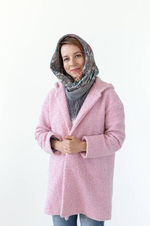 Cheerful young slim woman posing in pink coat with hood over white background. Concept of love for stylish unique things.