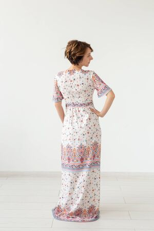 Rear view of a young slim woman in a long patterned dress standing against a white wall. The concept of unique products to order