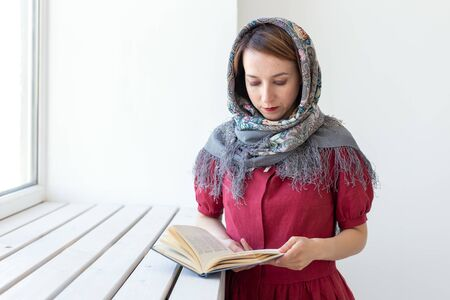 Close-up portrait of a cute young dreamy woman with a book in her hand looking out of the window and thinking about something. Concept lovers of classics and literature. Stock Photo