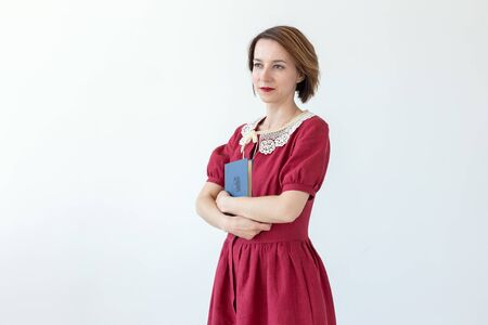 Portrait of cute smiling modest woman in dress holding classic book in hands on white background. Concept of lovers of history and classics. Copy space