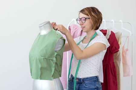 Positive cute smiling young seamstress woman in glasses with a measuring tape making a new garment with the help of a tailors dummy standing on a white background with ready-made designer products.