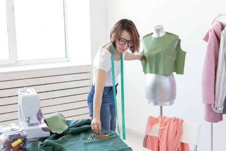 Young pretty girl seamstress designer with glasses and a measuring tape makes a new product with the help of a green cloth and a tailors dummy. Concept of sewing workshop. Stock Photo