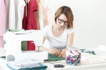 Young pretty girl student study at a clothes designer in college and does her first thesis sitting at a desk with a sewing machine. Clothing design concept.