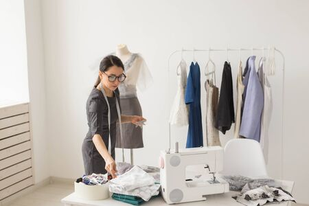 Dressmaker, tailor, fashion and showroom concept - Portrait of talented female dressmaker working with textile for sewing clothes Stock Photo