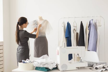 Dressmaker, technologies, fashion designer and tailor concept - young female fashion designer working in her showroom Stock Photo