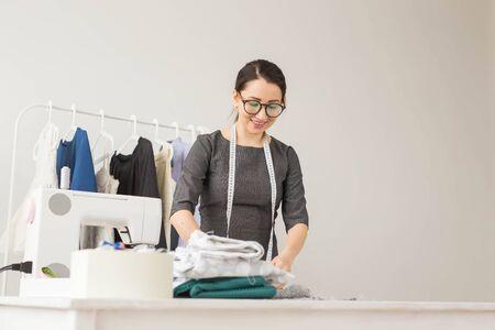 Dressmaker, fashion designer and tailor concept - young female fashion designer works in her showroom