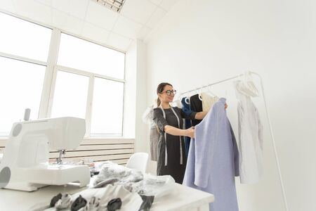 Dressmaker, fashion designer, tailor and people concept - young woman fashion designer in her showroom