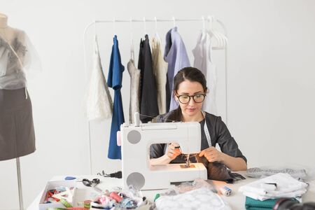 People, tailor, dressmaker and fashion concept - Smiling female fashion designer using sewing machine