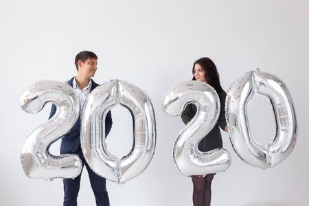 New year, celebration and holidays concept - love couple having fun with sign 2020 made of silver balloons for new year on white background Archivio Fotografico - 129855824