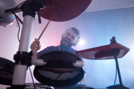 People, music and hobby concept - man playing drums over lighting background on the stage