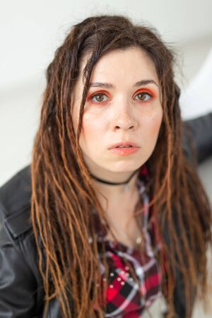 Fashion and beauty concept - young stylish woman in dreadlocks and colourful makeup