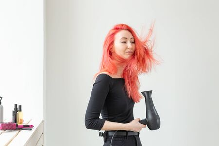 Stylist, fashion, hairdresser, people concept - woman drying her colored hair