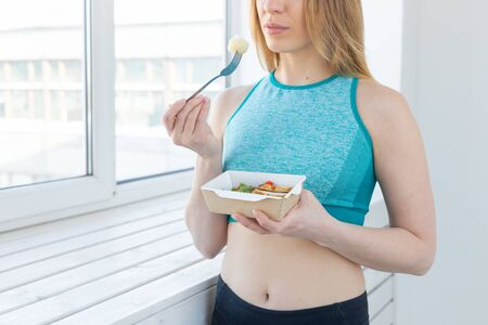 sport, healthy, people concept - Girl holding salad and dumbbell after fitness training Stock Photo