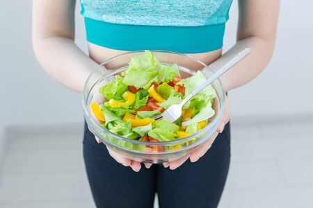 Healthy lifestyle and diet concept - Close-up of woman showing a vegetarian salad