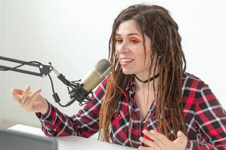 Radio host, blogging and broadcast concept - Modern party girl DJ in bright clothes and with dreadlocks