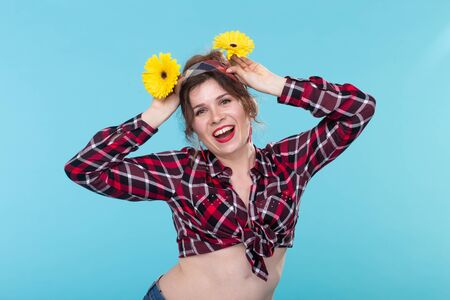 Vintage, fashion and floristic concept - woman with gerberas having fun in retro style on blue background