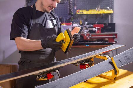 Repair, people concept - mechanic, man is rubbing a ski