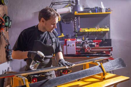 A man in work clothes repairman in the workshop ski service repairing the ski 스톡 콘텐츠