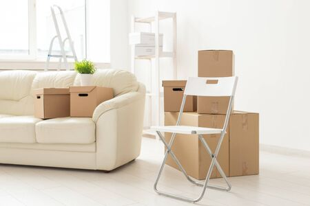 Folding chair sofa and boxes are in the new living room when residents move to a new apartment. The concept of new buildings and comfortable housing for young people. 版權商用圖片