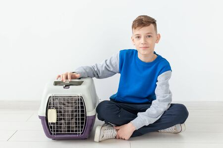 Laughing little positive boy holds a cage with a scottish fold cat next to him sitting on the floor in a new apartment. Pet protection concept.