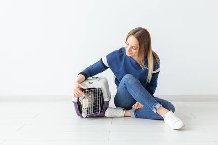 Positive good-looking woman and beautiful gray Scottish Fold cat into her new apartment after the move. Housewarming and pets concept.