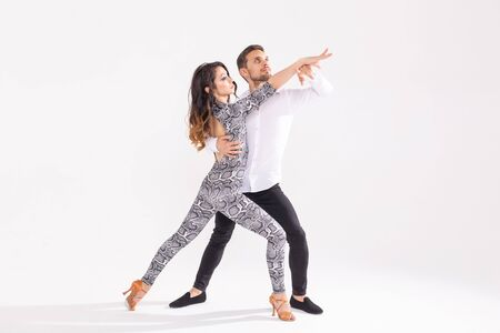 Young couple dancing latin dance bachata, merengue, salsa, kizomba. Two elegance pose over white background with copy space 免版税图像