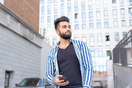 Modern arab young man with mobile phone in the street. Outdoor portrait.