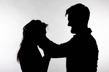 Domestic violence and abuse concept - Silhouette of man beating defenseless woman 写真素材 - 129875930