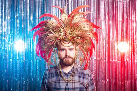 Fun, holiday and strange people concept - Funny man in carnival hat looking surprised