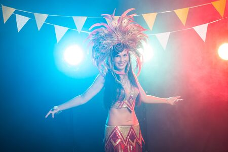Carnival, dancer and holiday concept - Beauty brunette woman in cabaret suit and headdress with natural feathers and rhinestones. 写真素材 - 129876090