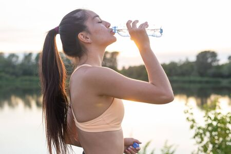 Fitness, outdoor training and people concept - Young woman drinking water after jogging Stock Photo