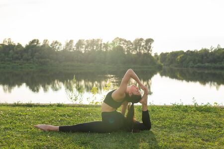 Harmony and healthy lifestyle concept - Young slim woman in sportswear practicing yoga outdoors. 写真素材