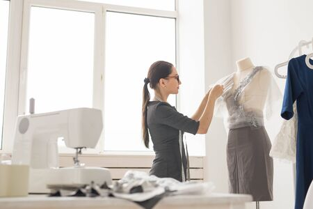 Dressmaker, tailor, fashion and showroom concept - Side view of female fashion designer measuring materials on mannequin in office 写真素材