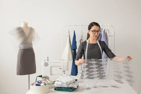 Dressmaker, tailor, fashion and showroom concept - Portrait of talented female dressmaker working with textile for sewing clothes 写真素材