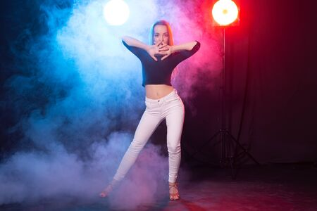 Dance, grace and elegance concept - young woman dancing bachata lady style in the dark, lights and smoke